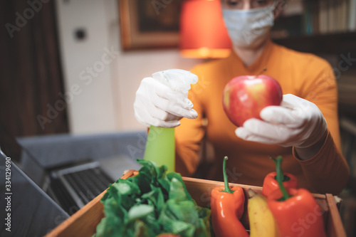 Obraz na plátně Woman with protective medical mask spraying sterilizing chemical on the food ordered from internet delivery