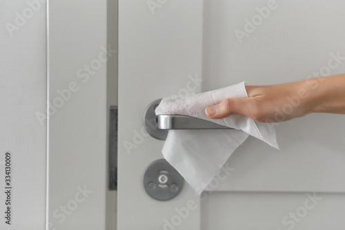 Obraz hygiene, health care and safety concept - close up of hand cleaning and disinfecting door handle surface with antiseptic wet wipe - fototapety do salonu