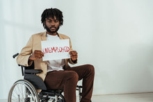 Disabled African American Man Looking At Camera And Holding Placard With Unemployed Lettering On Wheelchair On White