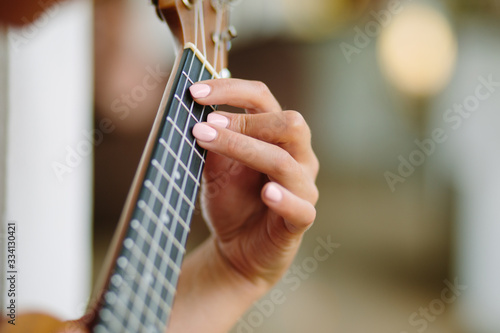 The girl plays on the ukulele, fingers clamping the chord of a guitar.