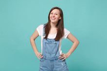 Smiling Young Brunette Woman Girl In Casual Denim Clothes Posing Isolated On Blue Turquoise Background Studio Portrait. People Lifestyle Concept. Mock Up Copy Space. Stand With Arms Akimbo On Waist.