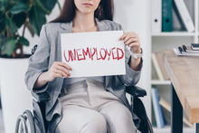Cropped View Of Disabled Employee Holding Placard With Unemployed Lettering On Wheelchair In Office