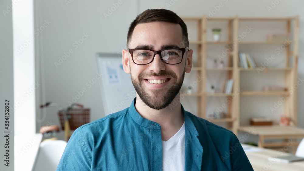 Fototapeta Headshot portrait of smiling Caucasian young man CEO or boss in glasses posing in modern office, happy motivated European male employee in spectacles show confidence and leadership at work
