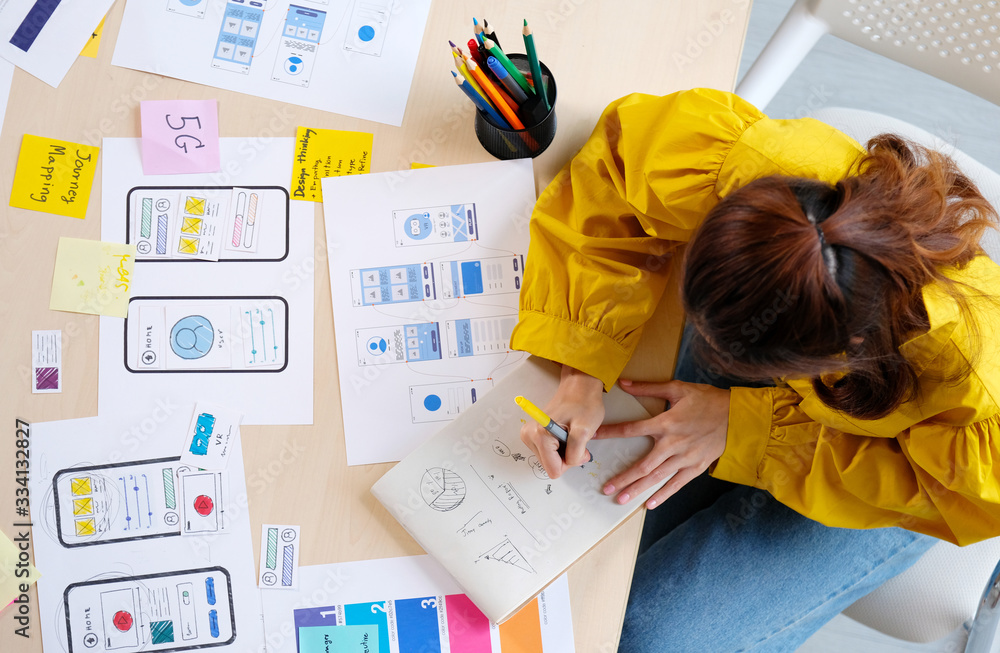 Fototapeta Website designer, Creative planning phone app development sketch template layout framework wireframe design, User experience, Overhead view of young woman UX designer thinking out web structure