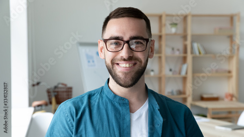 Headshot portrait of smiling Caucasian young man CEO or boss in glasses posing in modern office, happy motivated European male employee in spectacles show confidence and leadership at work