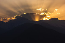 Crepuscular Light Rays Of The Setting Sun Scatter Behind The Himalayan Mountains And The Clouds In The Village Of Nako In Kinnaur In Himachal Pradesh, India.
