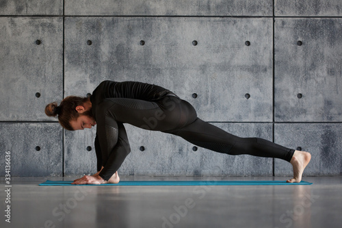 Photo A young bearded man in black comfortable sportswear is doing yoga indoors