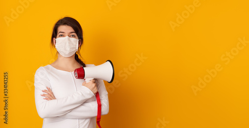 Photo Woman in medical mask with megaphone