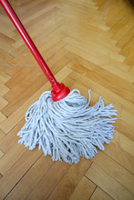 Isolated Cleaning Mop With Red Wooden Stick On Wooden Home Floor,parquet,  Cleaning And Disinfection Of Surfaces