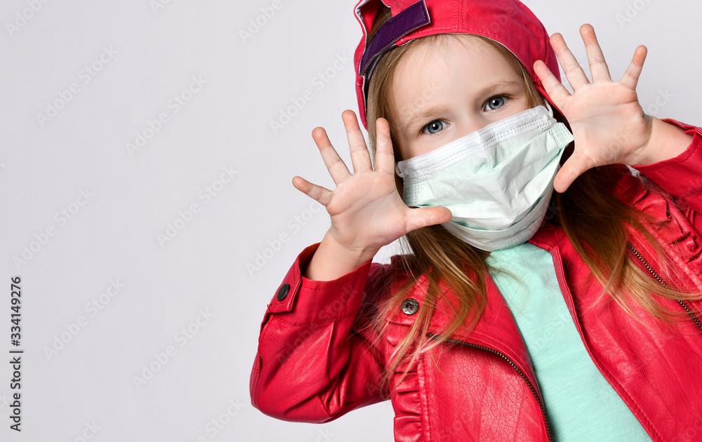 Fototapeta Potrait of playing blond baby girl in bright casual clothing wearing medical mask during coronavirus epidemic