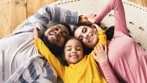 Fotografie, Obraz Family evening multiracial family. Daughter hugging parents