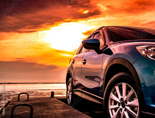 Fototapeta Blue luxury SUV car parked on concrete road by sea beach with beautiful red sunset sky. Summer vacation at tropical beach. Road trip. Front view sports and modern design SUV car. Summer travel by car. obraz