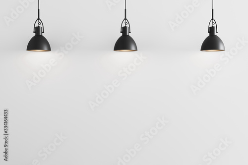 Fototapeta Three black pendant light on white wall background, ceiling lights, white wall w