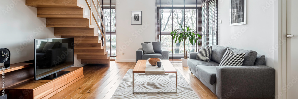 Fototapeta Living room with wooden stairs, panorama