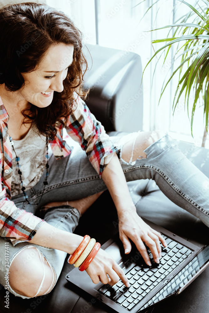 Fototapeta Smiling Woman Working on Laptop From Her Home. Working From Distance. Home Office