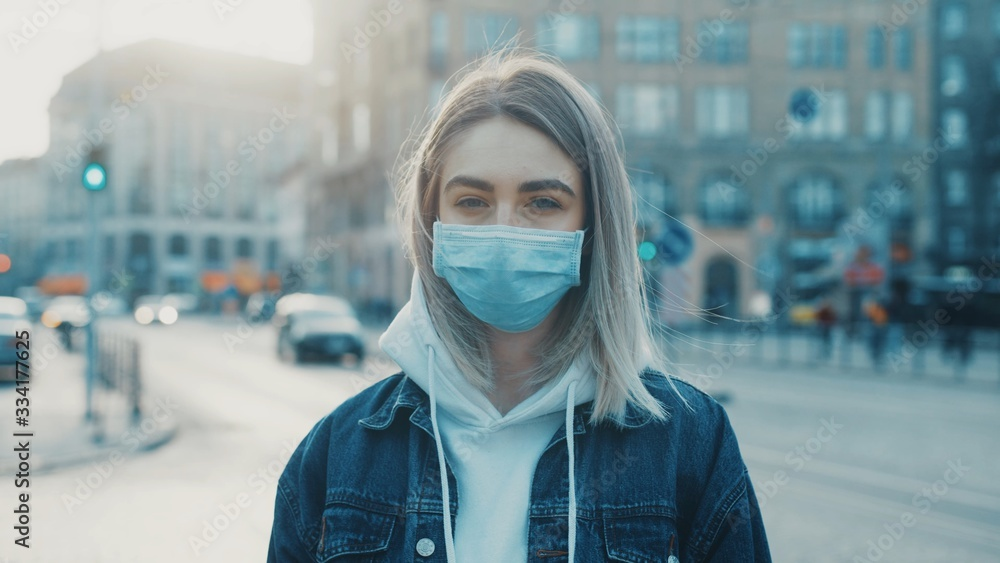 Fototapeta Young woman in medical mask standing in city street looking to camera road with cars on background Concept of health and safety life COVID-19 coronavirus virus protection pandemic in world