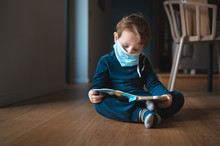 Baby Kid Sitting On The Floor Reading A Book With Surgical Mask On