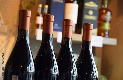 Wine bottles on wooden shelf in wine store Canvas Print