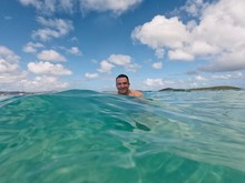 Dark Haired Man Swimming In Blue Ocean On Sunny Day With Clouds In The Sky.