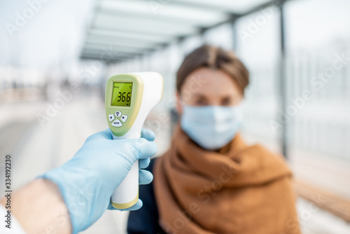 Photo Measuring temperature with infrared thermometer of a young woman in face mask at a checkpoint during an epidemic outdoors