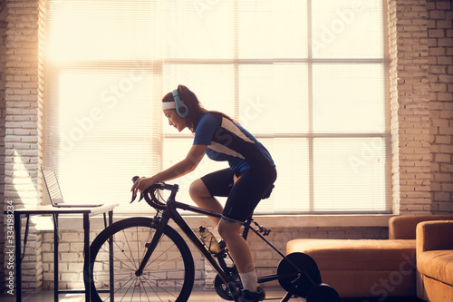 Fototapeta Asian woman cyclist. She is exercising in the house.By cycling on the trainer and play online bike games obraz