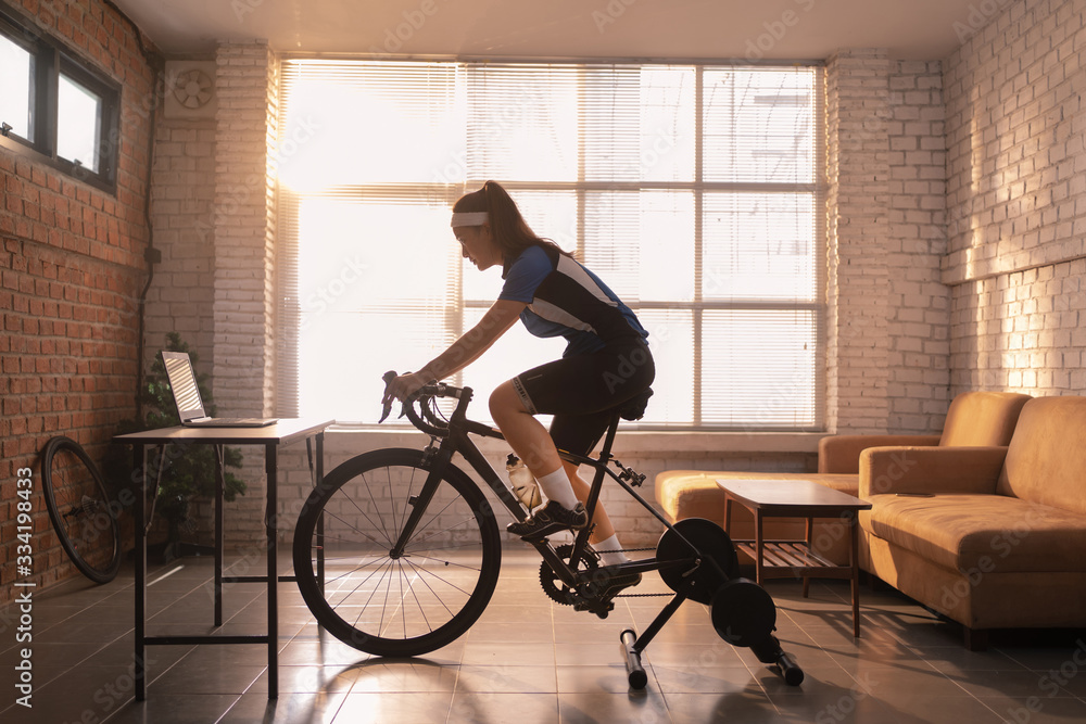 Fototapeta Asian woman cyclist. She is exercising in the house.By cycling on the trainer and play online bike games