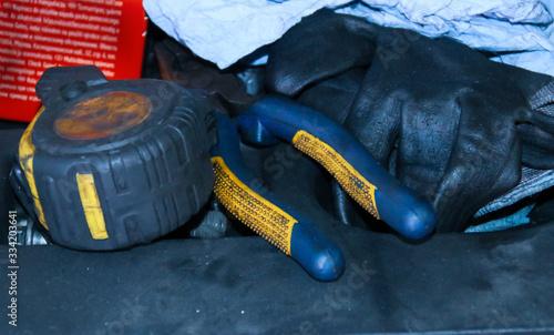 Photo Metro, alicates y guantes usados en un taller mecánico.