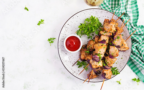 Fototapeta Grilled chicken kebab with red onions on a light table
