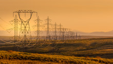 Electrical Power Lines Through A Rural Landscape At Sunset, USA