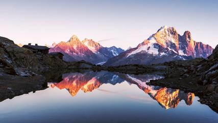 Colourful sunset on Lac Blanc lake in France Alps. Monte Bianco mountain range on background. Vallon de Berard Nature Preserve, Chamonix, Graian Alps. Landscape photography