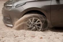 Car Wheels On A Sea Beach Sand. Close-up Of Car Wheel On Sandy Dunes In Countryside..Car Stuck In The Sand. Spinning Wheel Of A Car Stuck In The Sand.