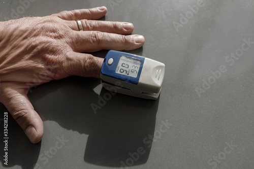 Photo Misuratore di ossigeno da dito su una mano, su sfondo grigio