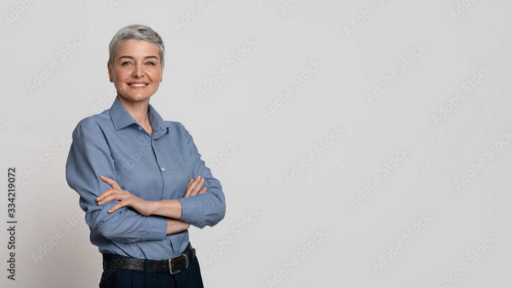 Fototapeta Portrait Of Mature Businesswoman Posing With Folded Arms Over Light Background