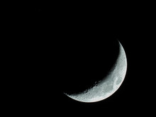 Increasing Sickle-shaped Quarter Moon With Its Moon Craters Stands In The Black Night Sky