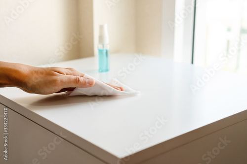 Woman hand cleaning headboard with disinfectant wet wipe and alcohol spray in bedroom at home Slika na platnu