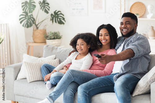 Fototapeta Smiling african american family relaxing and watching tv in living room