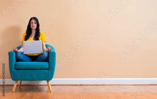 Stampa su Tela Young woman with laptop in a meditation pose pose sitting in a chair