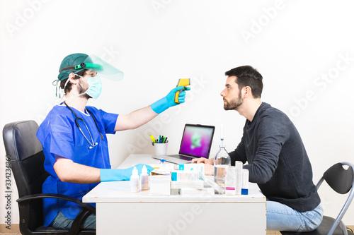 Coronavirus covid-19, medico sta facendo il test della febbre con il termometro laser al pre triage Wallpaper Mural