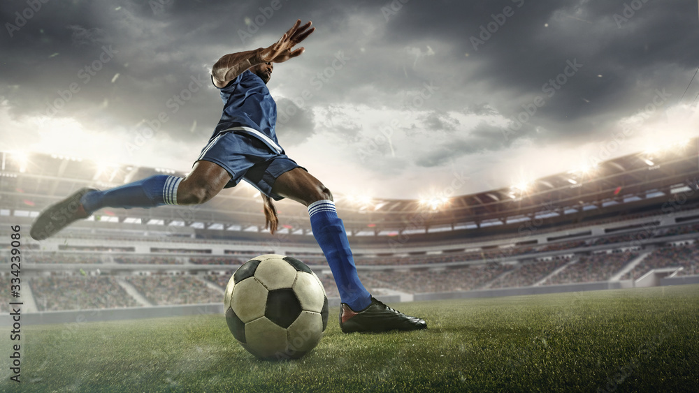 Fototapeta Professional football or soccer player in action on stadium with flashlights, kicking ball for winning goal, wide angle. Concept of sport, competition, motion, overcoming. Field presence effect.
