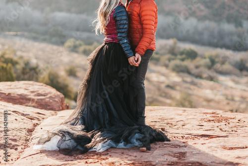 Fotografie, Obraz couple holding hands during adventure desert elopement