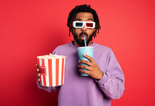 Boy Has Fun Watching A Film. Concept Of Entertainment And Streaming Tv. Red Background
