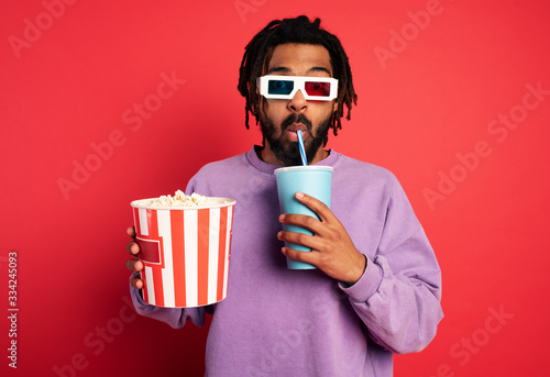 Obraz Boy has fun watching a film. Concept of entertainment and streaming tv. red background - fototapety do salonu