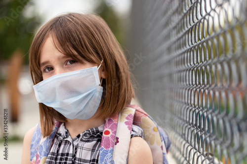 A school aged girl is longing to attend her closed school Canvas Print