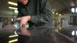 Worker in a green jacket polishes a marble table in a factory. Super Slow Motion