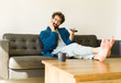 young cool man sitting on a sofa at living room watching tv or c