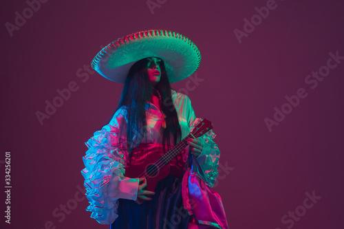 Fabulous Cinco de Mayo female dancer on purple studio background in neon light Billede på lærred