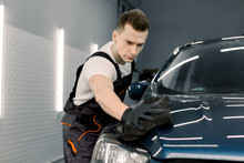 Young Car Wash Worker Man, Wearing Protective Clothes And Gloves, Cleaning Modern Dark Blue Car With Microfiber Cloth. Car Detailing Or Valeting Concept. Selective Focus On Face.
