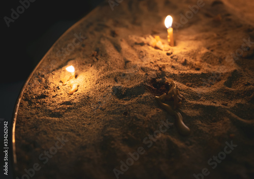 Three small burning candles on the sand burning out inside the church Canvas Print