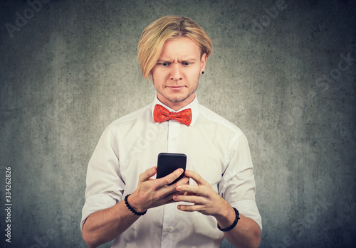 Photo Portrait of a baffled looking man reading bad news on his smartphone