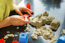 Cute Little Boy Age Of 3 Years Plays Kinetic Sand At Home. Occupation With A Child In Quarantine.